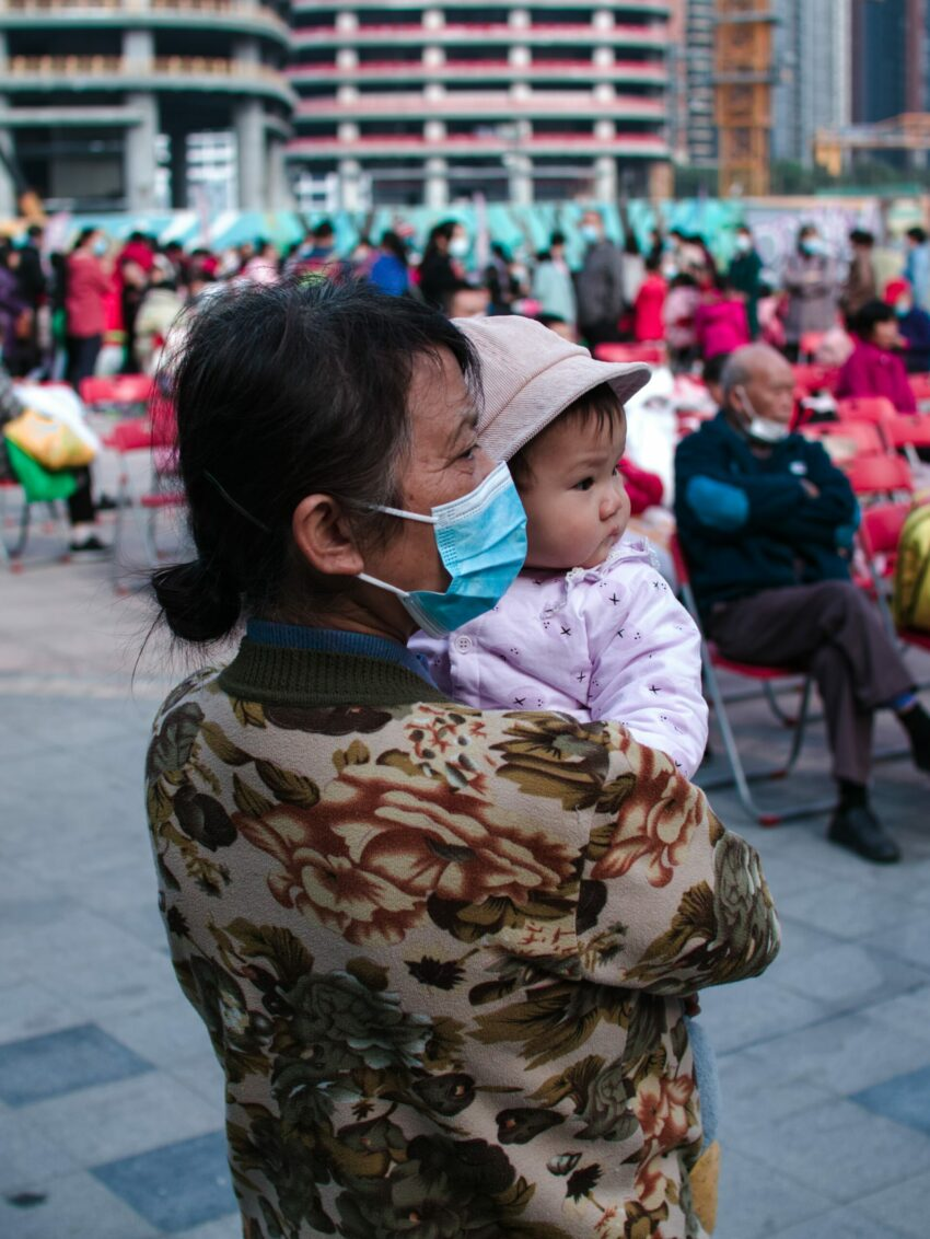 A woman in a mask holds a young baby watching a crowd.